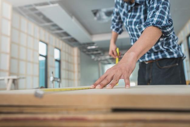 Dekorateur, der an entwurf arbeitet und des furnierholzes an der baustelle kontrolliert; dekorateur, der material auf innenraum überprüft