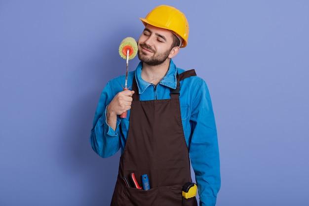 Dekorateur mit farbroller in den händen berührt seinen bart und hält die augen geschlossen, mann trägt helm und braune schürze
