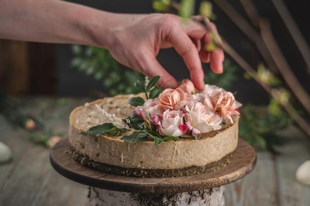 Dekorateurhand, die den moussekuchen mit zarten rosa blumen verziert