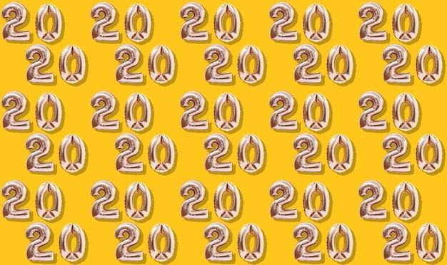 Dekoration 2020 des neuen jahres aufblasbare goldzahlen auf dem gelben hintergrundmuster.