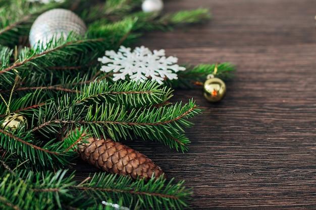 Dekoration der grünen zweige des weihnachtsbaumes auf einem braunen hintergrund mit kopienraum