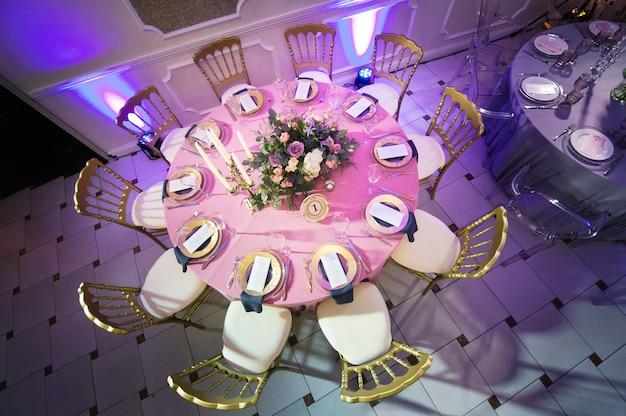 Dekoration des festlichen abendessens mit blumen aus lilien und tulpen auf dem hochzeitstisch im inneren des restaurants. dekorierter tisch zum feiern.