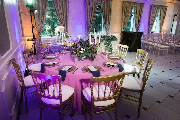 Dekoration des festlichen abendessens mit rosenblüten auf dem hochzeitstisch im inneren des restaurants. dekorierter tisch zum feiern.