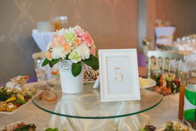 Dekoration des gästetischs mit einem schild 5 und blumen in einer weißen vase