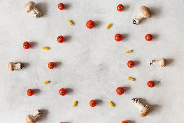 Dekoration des gemüses und der fusilli im kreisrahmen auf weißem hintergrund