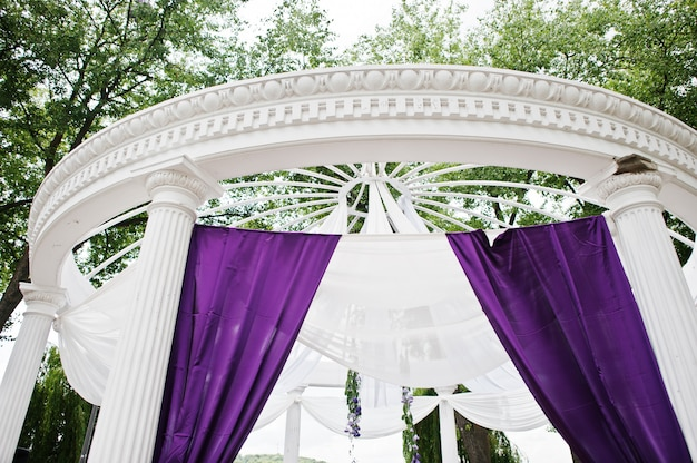 Dekoration des hochzeitsbogens mit violettem und weißem stoff