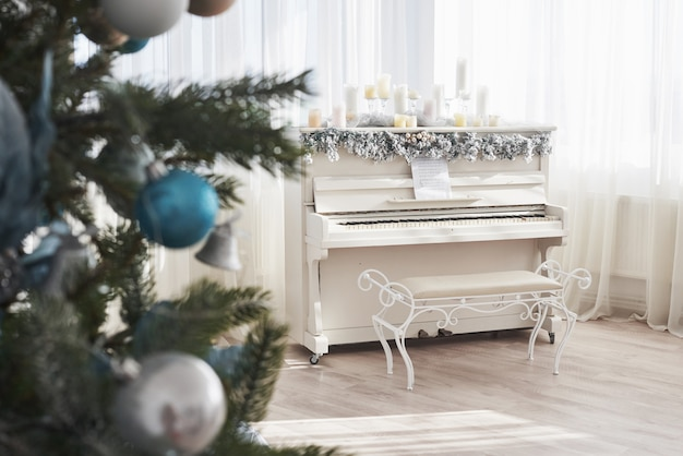 Dekoration des neuen jahres. weihnachtsbaum nahe weißem klavier am fenster