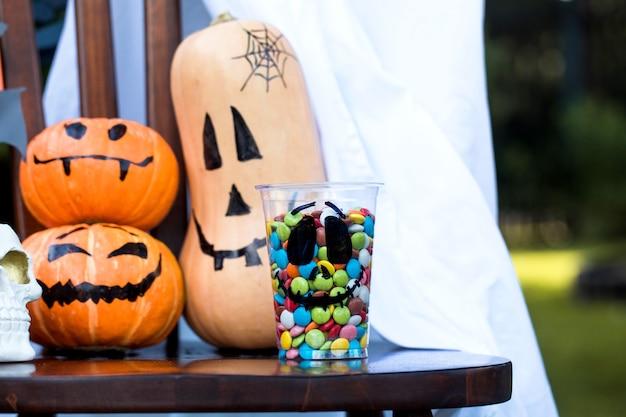 Dekoration für halloween kürbisse mit gruseligen gesichtern bunte bonbons und süßigkeiten