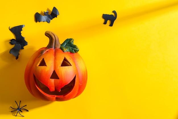 Dekoration für halloween-party mit kürbislaterne und geschnittenen handgemachten fledermäusen, katze und spinne auf gelbem hintergrund
