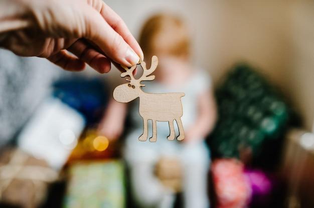 Dekoration in form von hirschen. porträt glückliches kleines mädchen, das mit geschenken spielt. festliches geburtstagskonzept. baby auf foto. säugling. frohe weihnachten, schöne feiertage. neujahr.