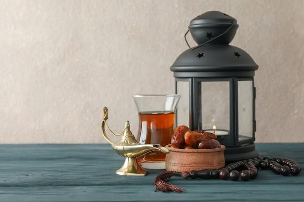 Dekoration und essen des ramadan kareem-feiertags auf holztisch gegen hellen hintergrund