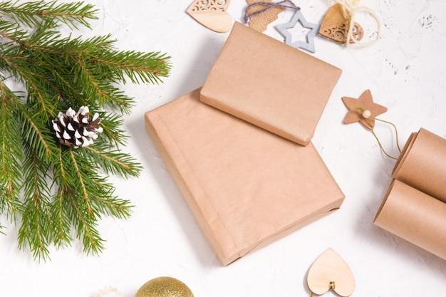 Dekoration von weihnachtsgeschenken im öko-stil, papier zum verpacken, dekor aus naturmaterialien und geschenkboxen auf weißem hintergrund, hausgemachtes dekor für weihnachten und neujahr, mock-up