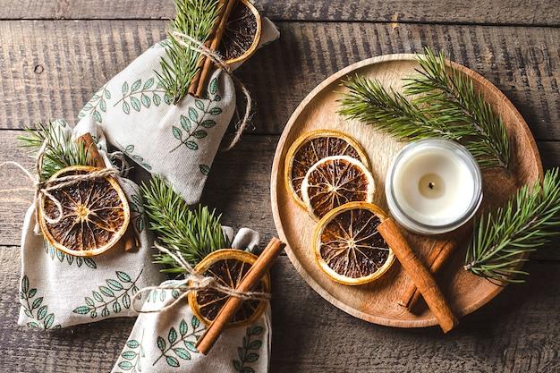 Dekoration von weihnachtsgeschenken mit trockener orange, zimt, tanne. umweltfreundliche textil-geschenkverpackung. ansicht von oben, flach