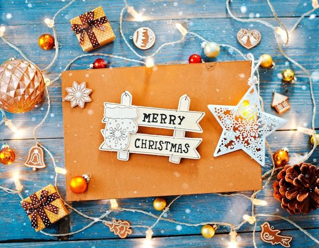 Dekorationen des neuen jahres um leeren raum des weihnachtsbriefs für brennende lichtgirlanden des textes auf blauem hölzernem hintergrund.