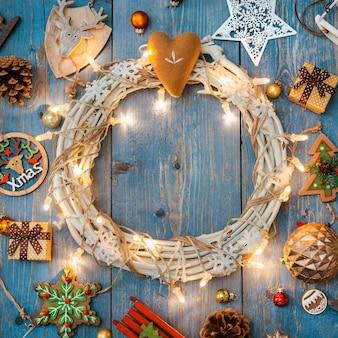 Dekorationen des neuen jahres um weihnachtskranz auf blauem hölzernem hintergrund.
