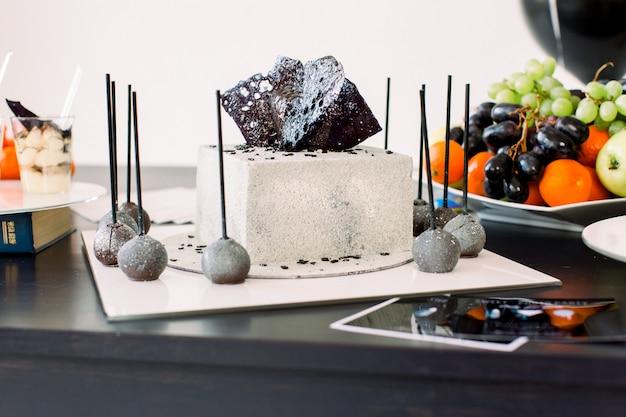 Dekorationen für die geburtstagsfeier. stilvolle weiß und schwarz dekorierte geburtstagstorte, köstliche desserts und frische früchte auf dem schwarzen tisch. geburtstagsfeier-konzept, kuchen, desserts, schokoriegel