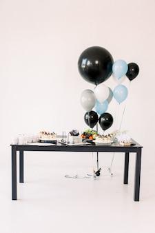 Dekorationen für die weihnachtsfeier. viele luftballons in den farben blau, schwarz und weiß. schwarzweiss-geburtstagsfeierdekoration, schwarzer tisch mit voller kuchen und süßer süßigkeit