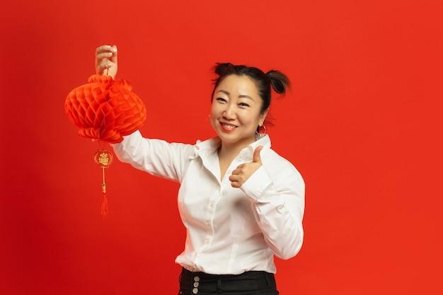 Dekorationen für stimmung. . asiatische junge frau, die laterne auf roter wand in traditioneller kleidung hält. lächelnd, daumen hoch. feier, menschliche gefühle, feiertage. copyspace.
