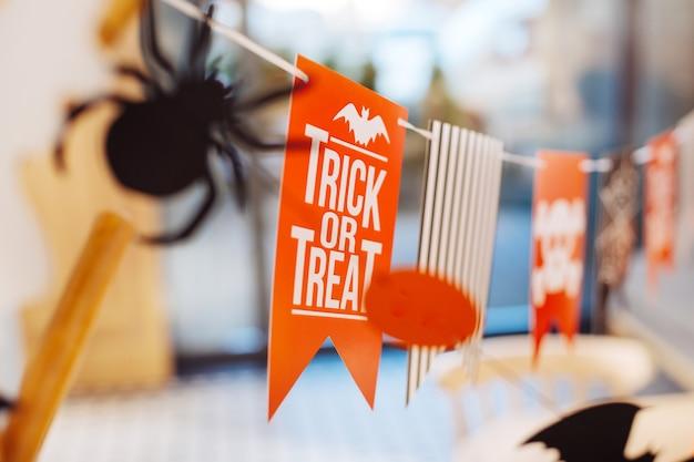 Dekorationen präsentieren. professionelle eventmanager präsentieren ihre halloween-dekoration mit süßes oder saures-zeichen