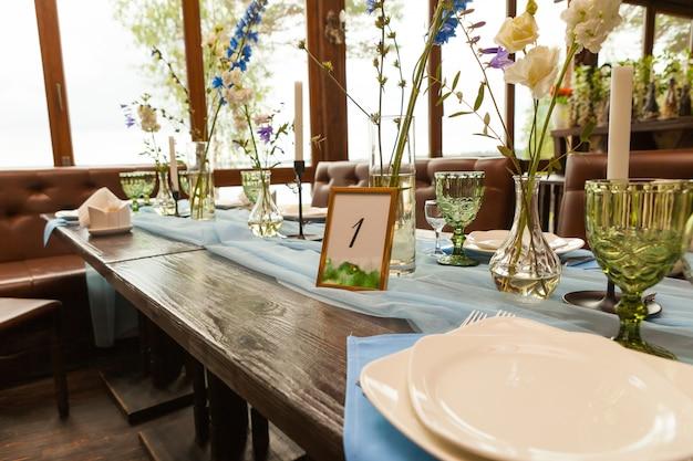 Dekorationen und wildblumen dienten auf der festlichen tabelle und heirateten feierkonzept