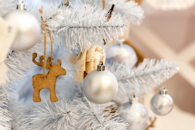 Dekorationsbälle der weißen weihnacht, die an einem dekorativen weißen weihnachtsbaum hängen. feierhintergrund des konzept-neuen jahres.