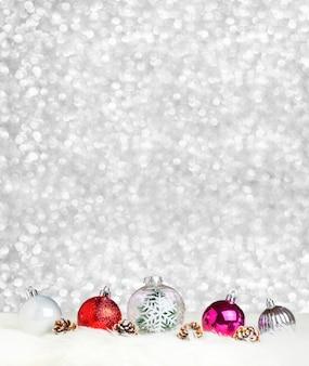 Dekorationsball der frohen weihnachten auf weißem pelz am silbernen bokeh lichthintergrund