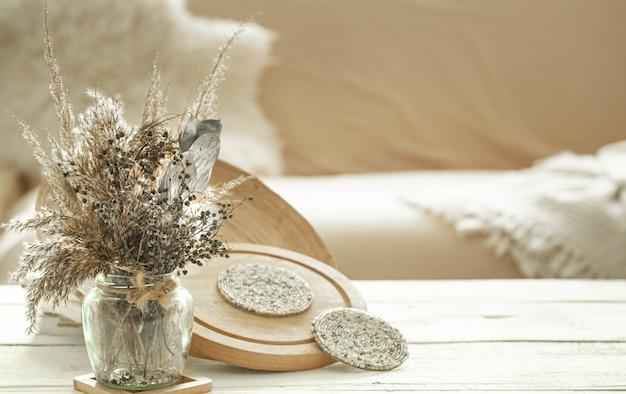 Dekorationsgegenstände im gemütlichen innenraum des raumes, eine vase mit getrockneten blumen auf hellem holztisch.