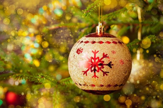 Dekorationskugel auf verziertem weihnachtsbaumhintergrund
