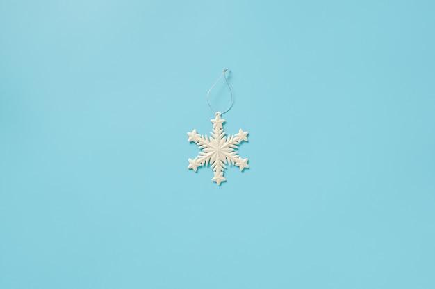 Dekorationsschneeflockenspielzeug der weißen weihnacht auf blauem hintergrund. frohe weihnachten oder ein gutes neues jahr.