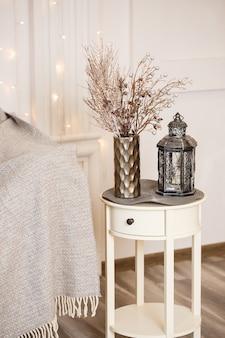 Dekorative antike silberne retro-lampe auf einem weißen kleinen tisch im wohnzimmer. inneneinrichtung im haus.