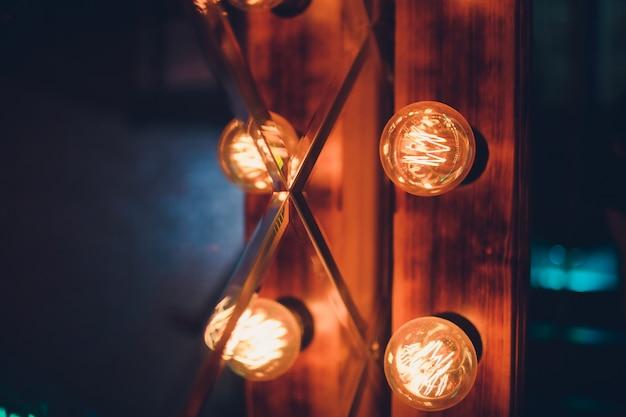 Dekorative antike wolframlampen im edison-stil vor backsteinmauer-hintergrund.