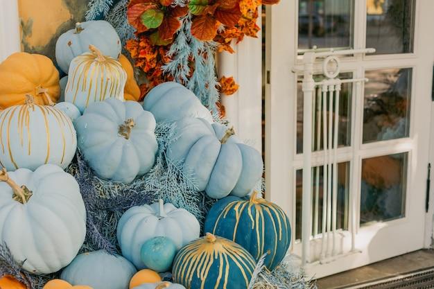 Dekorative blaue und orangefarbene kürbisse im freien blumen und halloween-dekorfassade im freien