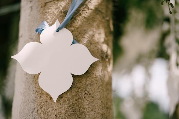 Dekorative blume des weißen papiers, die von einem band auf einer säulenhochzeitsdekoration hängt