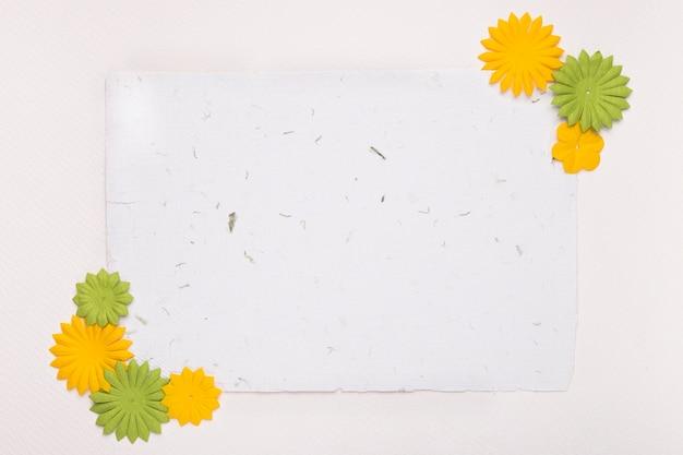 Dekorative blumen an der ecke des leeren papiers gegen weißen hintergrund