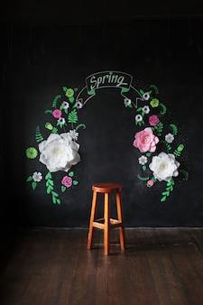 Dekorative blumen aus papier an einer schwarzen wand. ein dekorativer rahmen aus papierblumen. die zeichnungskreide auf einer tafel