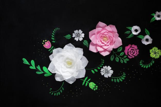 Dekorative blumen aus papier auf schwarzer oberfläche. kreide auf eine tafel zeichnen.