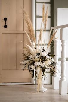 Dekorative blumenanordnung von getrockneten blumen in der vase steht auf der veranda des dorfhauses