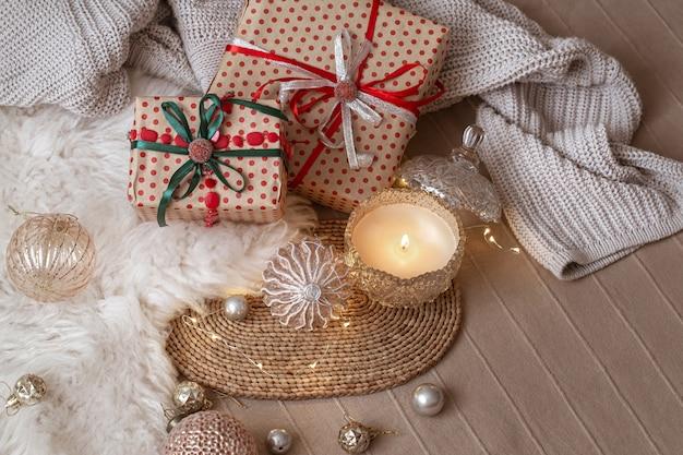 Dekorative brennende kerze auf dem hintergrund von weihnachtsgeschenken mit gemütlichen dingen und dekordetails schließen.