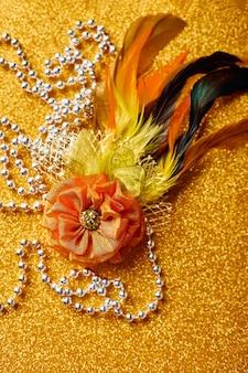 Dekorative brosche mit federn für karneval oder karnevalsmaske und perlen auf goldenem hintergrund partyeinladungsgrußkarte venezianischer karnevalsfeierkonzept
