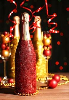 Dekorative champagnerflaschen mit weihnachtskugeln auf dunklem hintergrund