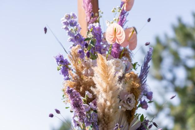 Dekorative dekoration des hochzeitsbogens mit frischen blumen. eine hochzeitszeremonie im freien abhalten. dekorationsdetails.