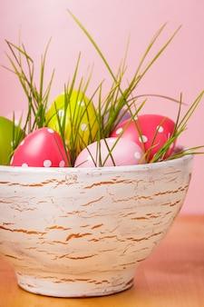 Dekorative eier im topf mit gras über rosa hintergrund. osterdeko.