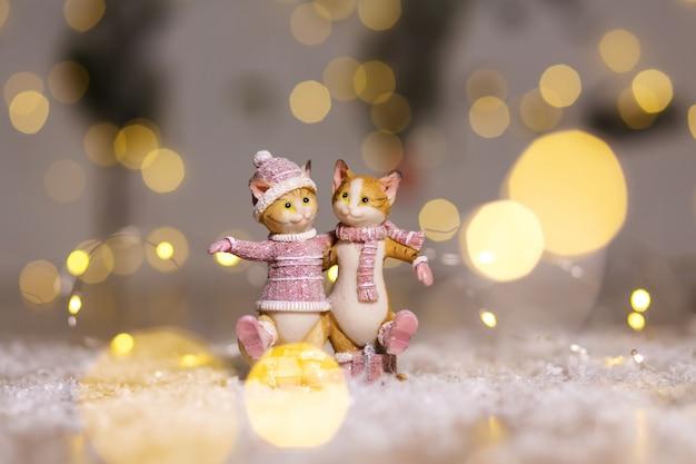 Dekorative figuren eines weihnachtsthemas. figur von niedlichen umarmenden katzen, gekleidet in einen gestrickten pullover, einen schal und eine mütze