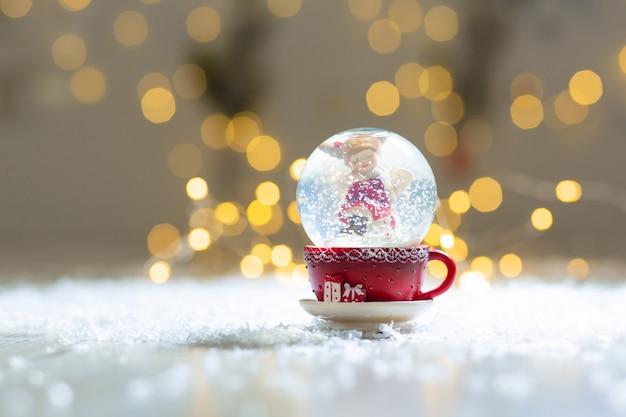 Dekorative figuren eines weihnachtsthemas. glaskugel mit schneeflocken, in der ein weihnachtsengel sitzt.