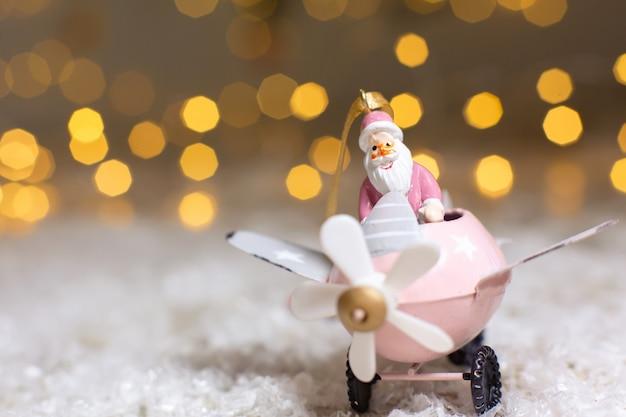 Dekorative figuren eines weihnachtsthemas, weihnachtsmann in einem rosa flugzeug mit propeller,