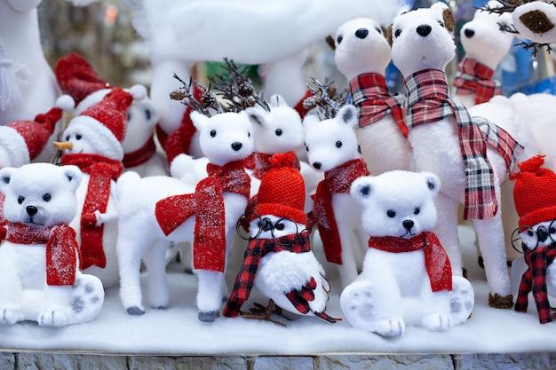 Dekorative figuren zu weihnachtsthemen. satz weihnachtsfiguren von rotwild, von eulen und von schneemann in den roten schals. weihnachtsdekorationen. festliche einrichtung. weihnachtshirsch. weihnachtsdekoration. neues jahr 2020