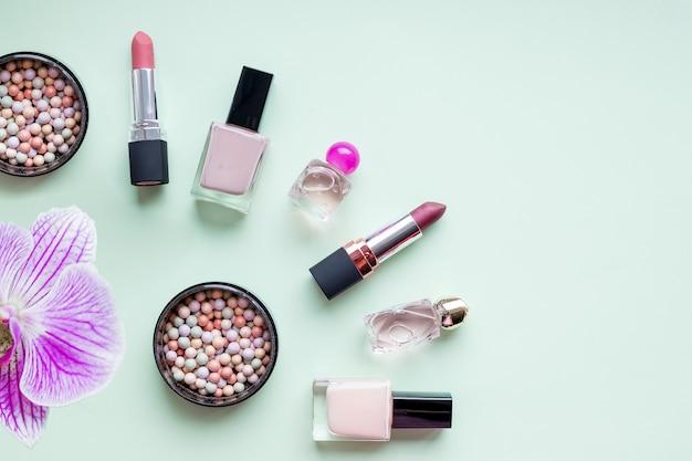 Dekorative flache komposition mit lippenstift und rouge, verziert mit blumen. draufsicht auf weichem grünem hintergrund.stylish designhintergrund. kreatives modisches konzept. werkzeuge der frauenschönheit