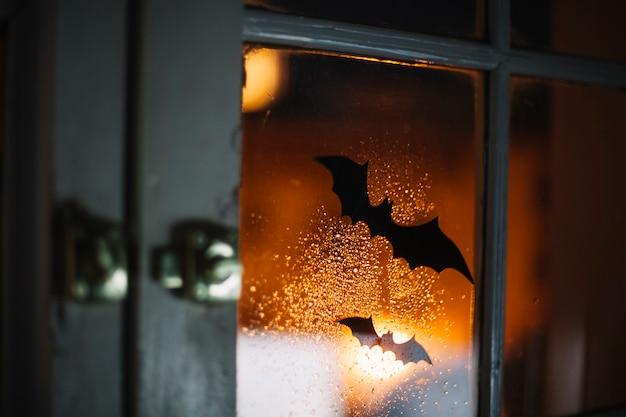 Dekorative fledermäuse halloweens auf fenster mit regentropfen