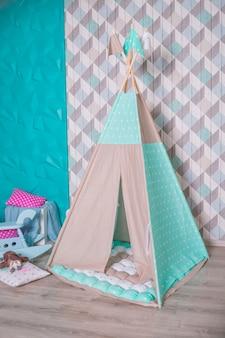 Dekorative gemütliche hütte im boho-stil mit dekor. kinderzimmer im skandinavischen stil, innenarchitektur. tipi-zelt für kinder, spielzelt für kinder, skandinavisches design, farbenfroh.