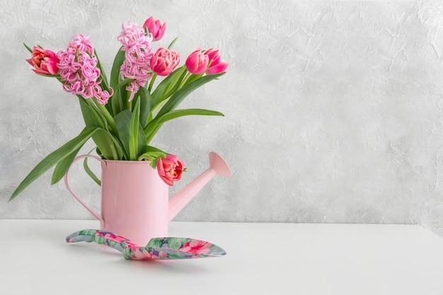 Dekorative gießkanne mit rosa tulpen.